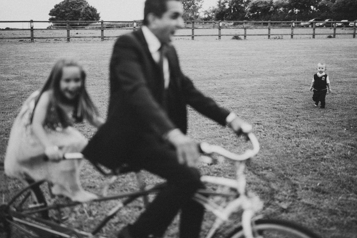 wedding outdoor field fun on a tandem bicycle