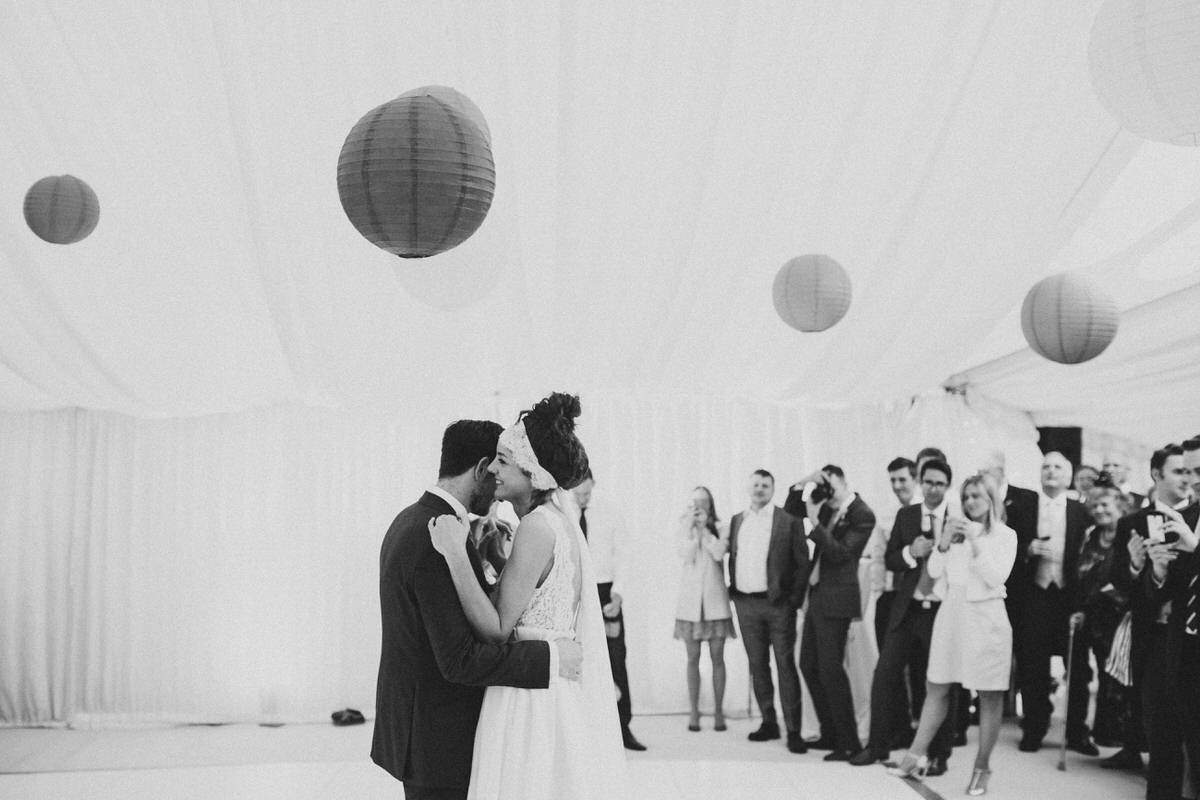 black and white first dance photos in a marquee